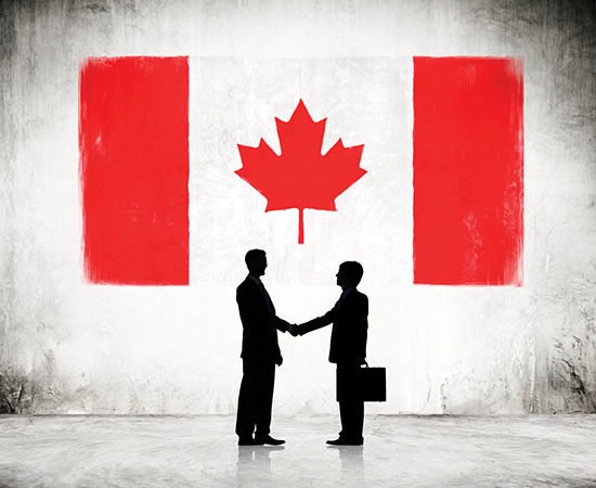 Businessmen Shaking Hands with Canadian Flag