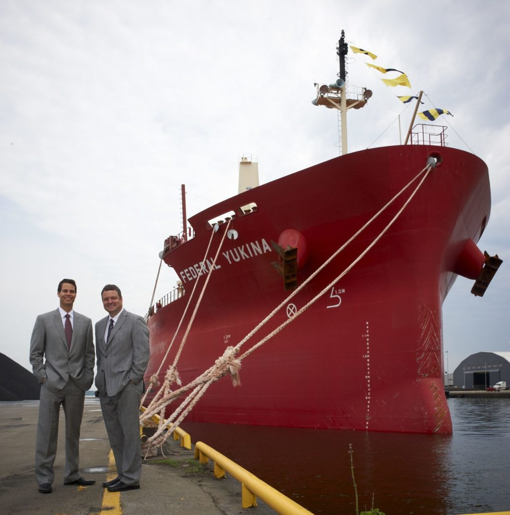 Paul Pathy, president and co-CEO of Fednav Group and Bruce Wood, president and CEO of Hamilton Port Authority, stand next to the Federal Yukina at Federal Marine Terminals at the Port of Hamilton.