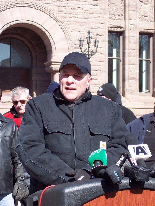 Protest organizer Scott Mooney speaks to the media during today's protest.