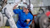Asian factory worker woman hold tablet and maintenance with check part of robotic machine in workplace area